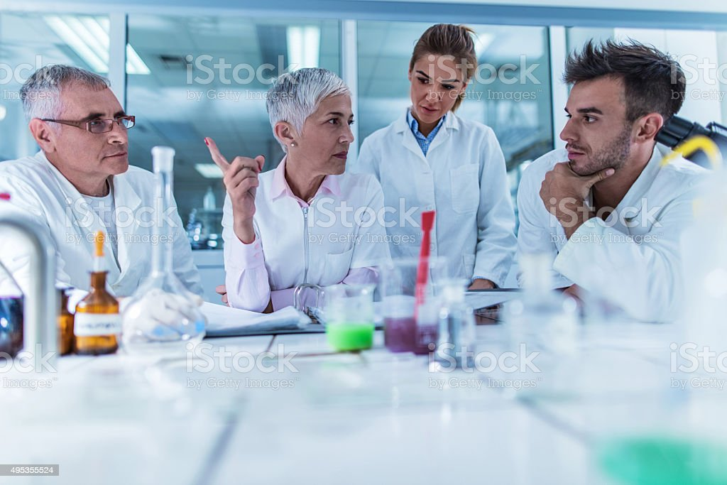 Group of scientist communicating on a meeting in laboratory. stock photo