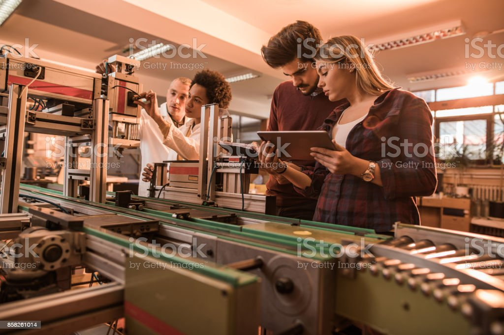 Group of scientist working on engineering project in a laboratory. stock photo