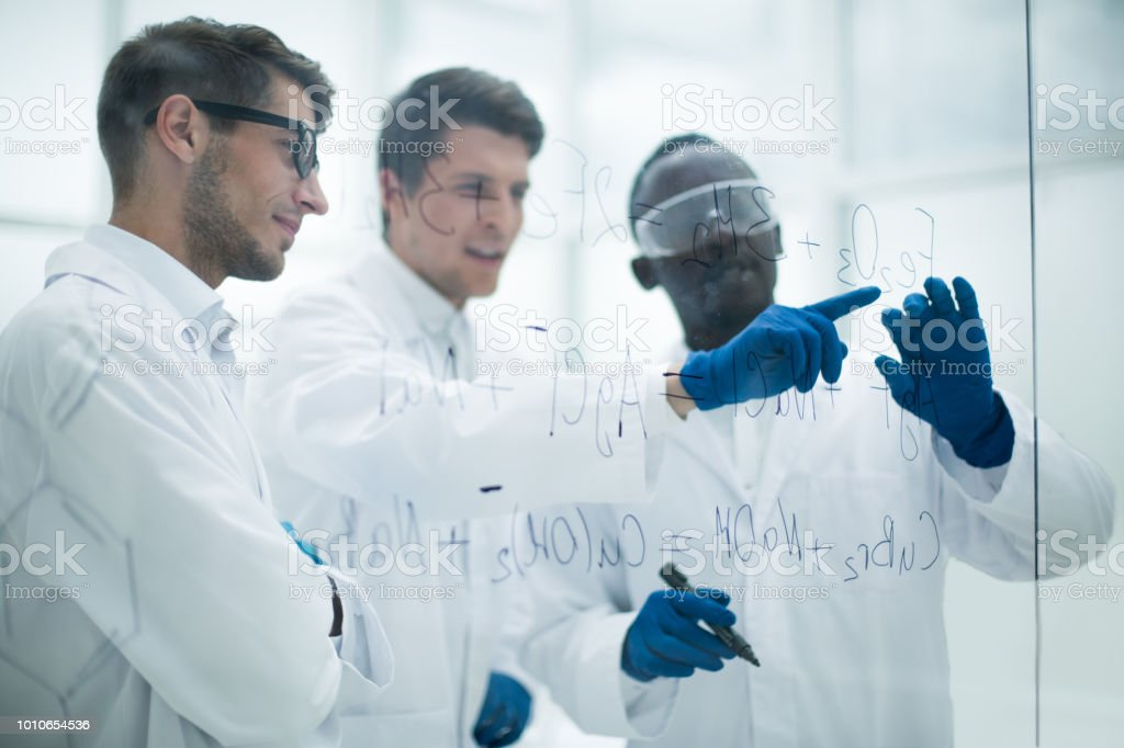 group of scientists discusses the information and makes notes stock photo