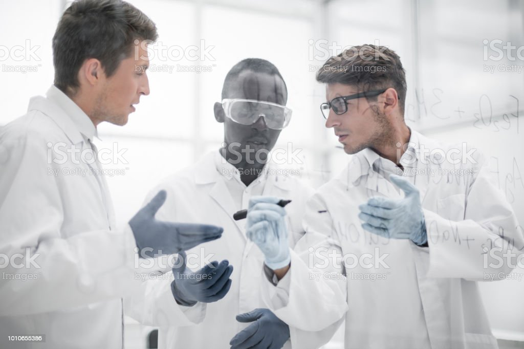 group of scientists discussing chemical formulas stock photo