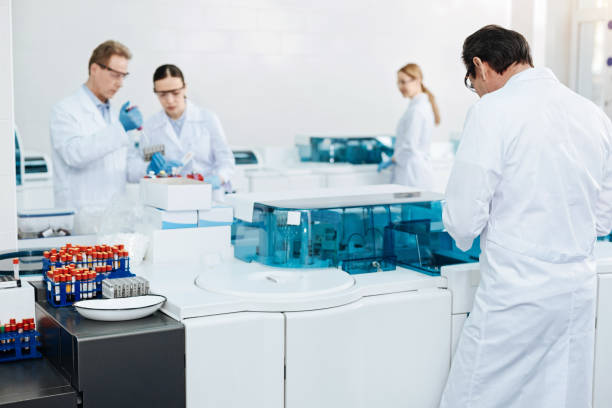 Group of scientists working together Active process. Two colleagues standing near glass holder bowing heads while examining blood dna purification stock pictures, royalty-free photos & images