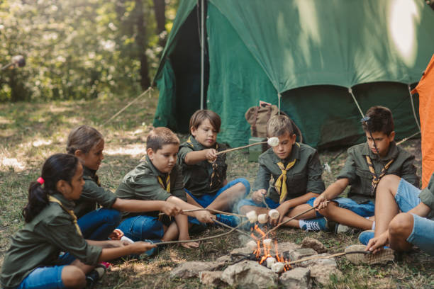 Group Of Scouts Roast Marshmallow Candies On Campfire In Forest