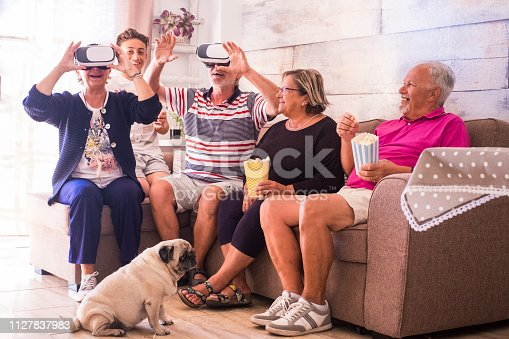 Group of senior adult caucasian people family enjoying the leisure indoor day having fun together with goggles headset technology and cinema popcorn - mixed ages generations people with old funny dog at home