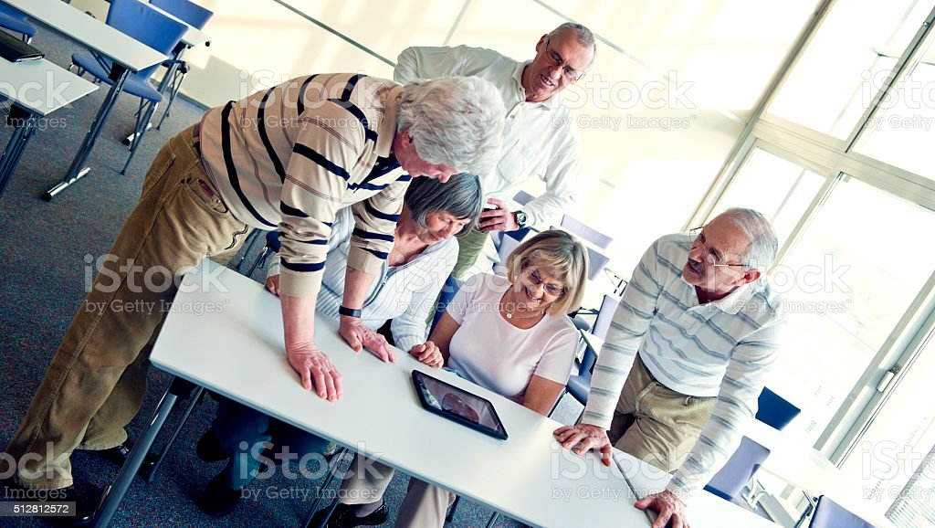 Group of senior adult having fun with digital tablet stock photo