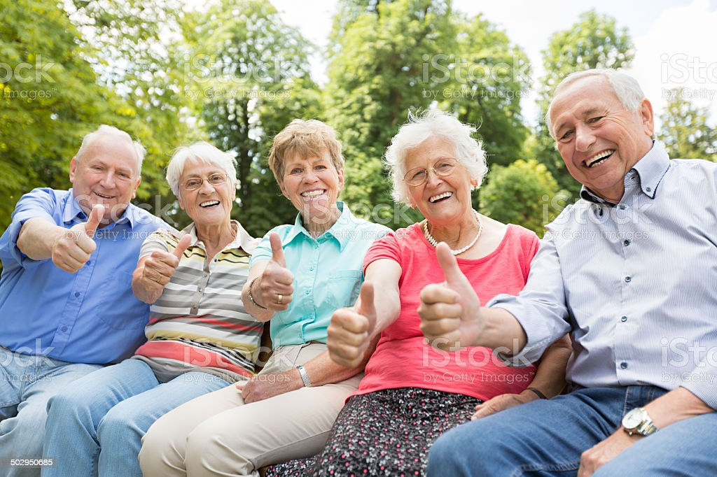 Group of senior adult in the park showing thumbs up stock photo