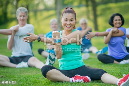 646614234 istock photo A group of senior adults are taking a fitness calss outside at the park. They are sitting on the grass and are stretching together. 646614224