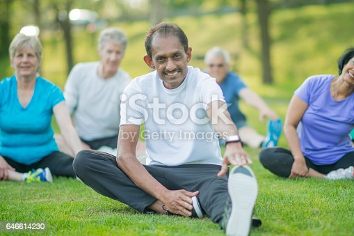 646614234 istock photo A group of senior adults are taking a fitness calss outside at the park. They are sitting on the grass and are stretching together. 646614230