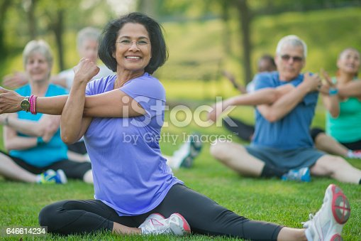 istock A group of senior adults are taking a fitness calss outside at the park. They are sitting on the grass and are stretching together. 646614234