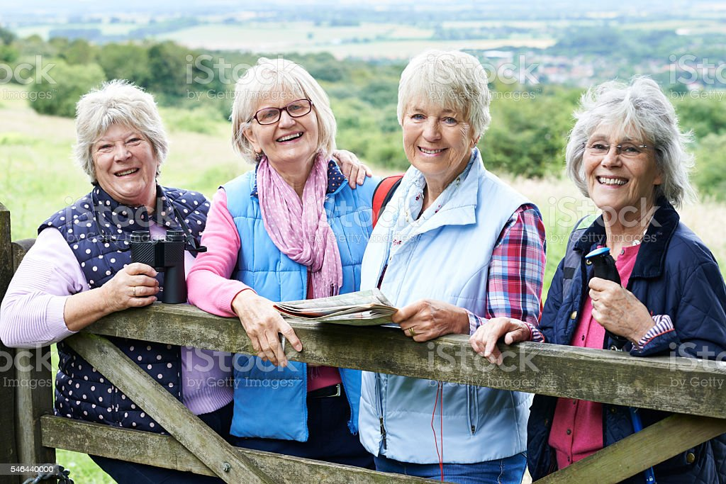 Group Of Senior Female Friends Hiking In Countryside stock photo