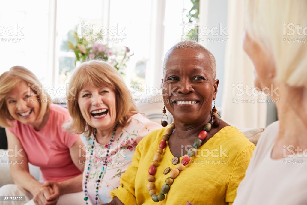 Group Of Senior Female Friends Relaxing On Sofa At Home стоковое фото