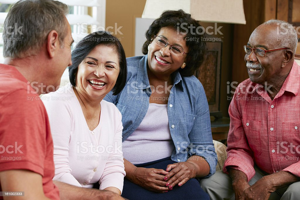 Group Of Senior Friends Chatting At Home Together stock photo