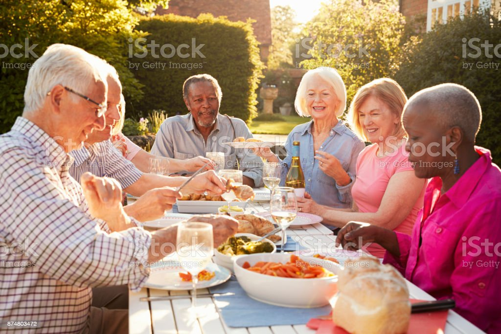 Group Of Senior Friends Enjoying Outdoor Dinner Party At Home стоковое фото