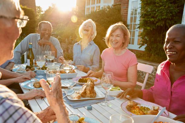 groupe d'amis hauts profiter de dîner en plein air à la maison - diner entre amis photos et images de collection