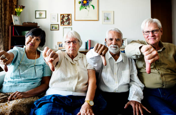 Group of senior friends gesturing thumbs down sign Group of senior friends gesturing thumbs down sign critic stock pictures, royalty-free photos & images