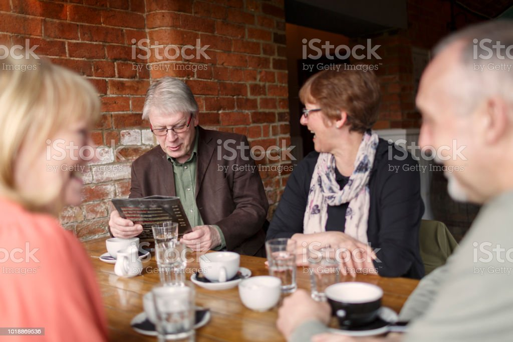A group of senior friends having fun and drinking coffee in a bar stock photo