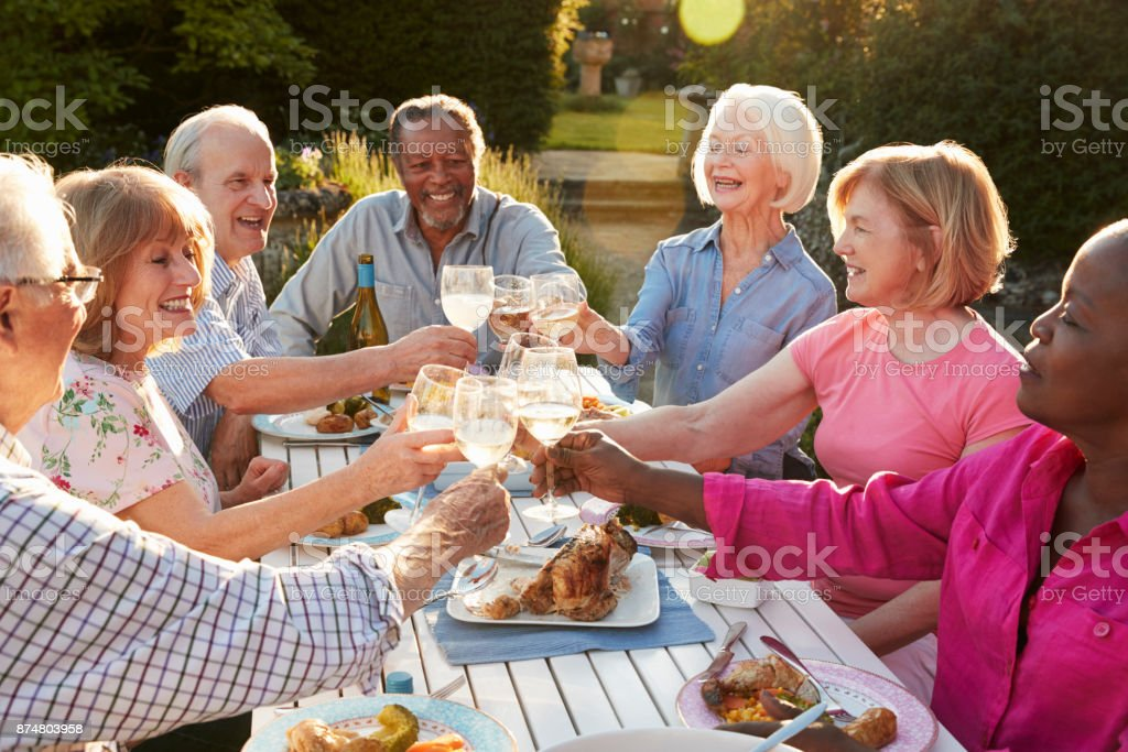 Group Of Senior Friends Making A Toast At Outdoor Dinner Party стоковое фото