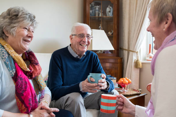 group of senior friends meeting at home for coffee - elderly group stock photos and pictures