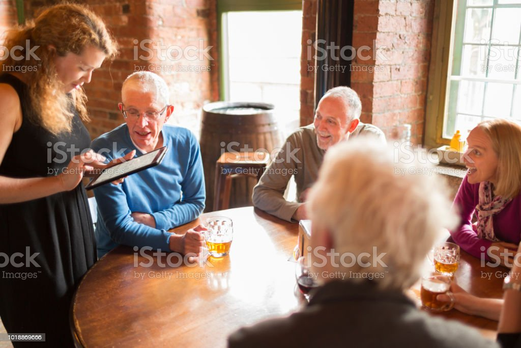 A group of senior friends ordering food and drinks from a waitress in a restaurant bar stock photo