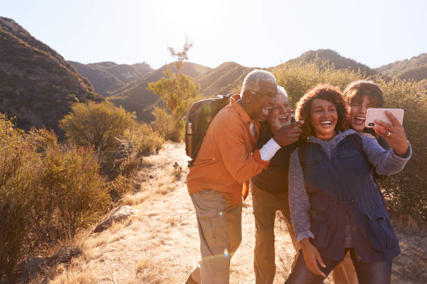 Group Of Senior Friends Posing For Selfie As They Hike Along Trail In Countryside Together stock photo