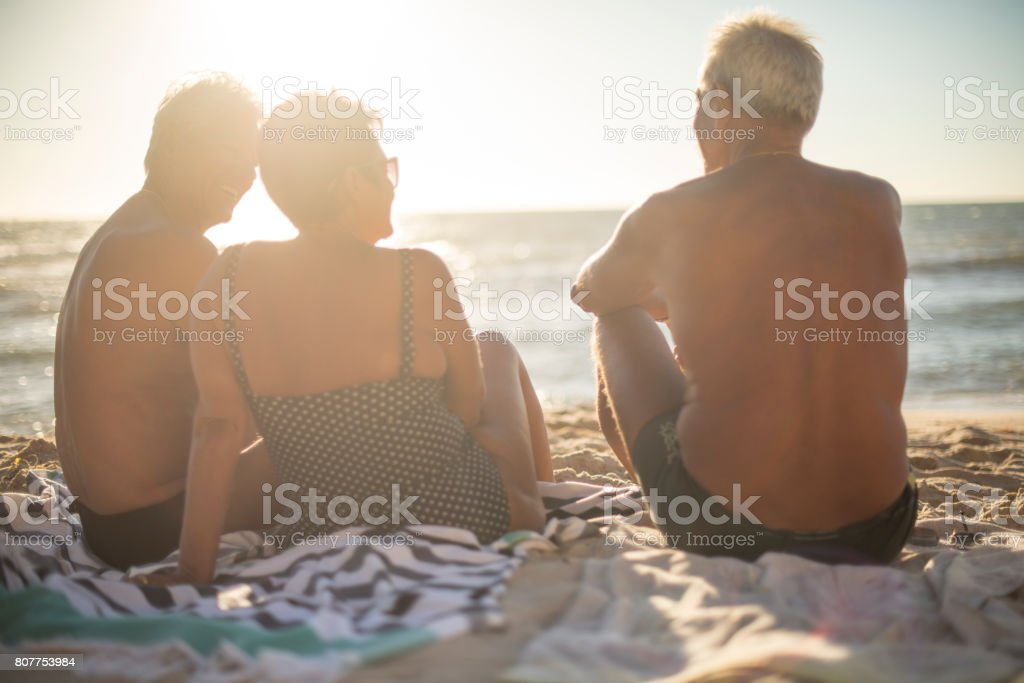 A group of senior friends relaxing at the beach in summer royalty-free stock photo