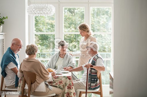 istock Group of senior friends with helpful carer sitting together at the table at nursing home dining room 1147156037