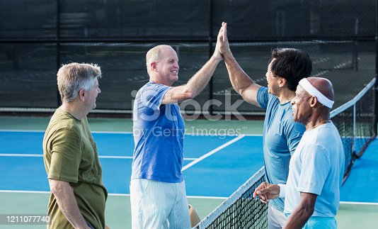 A multi-ethnic group of four mature and senior men on a pickleball court, standing at the net giving each other high-fives. The African-American man is the oldest, in his 70s.
