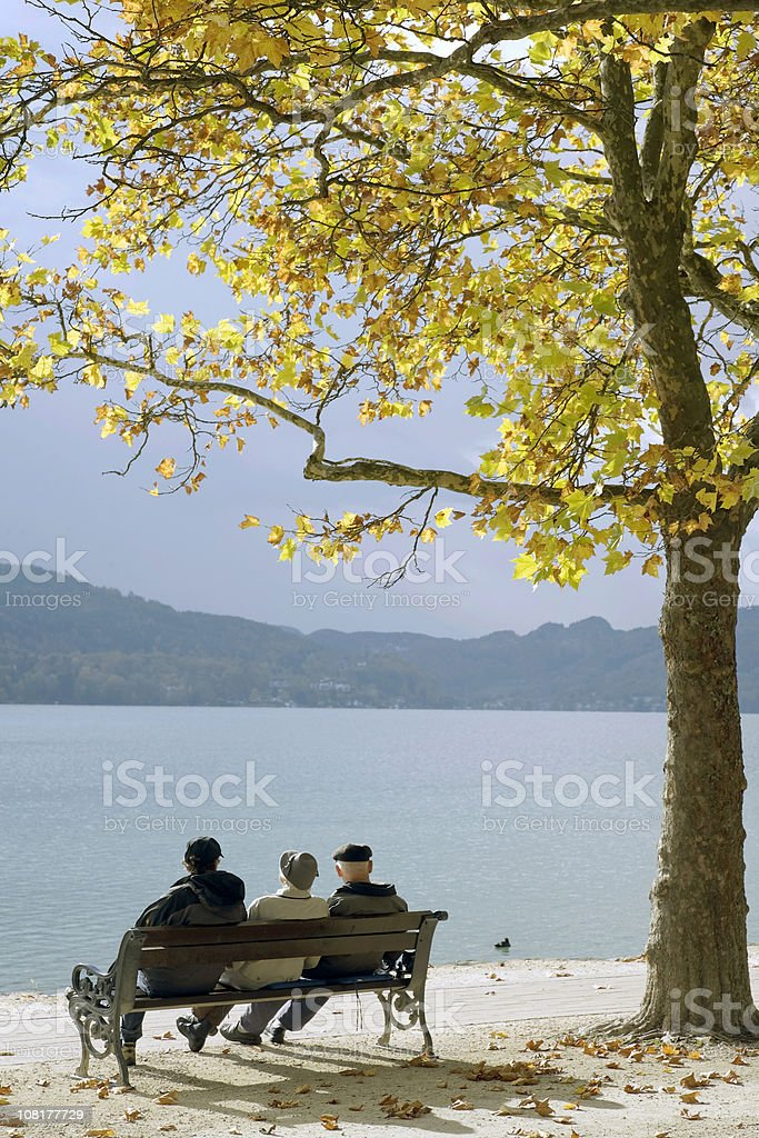 Group of Senior Men sitting on Lakeside Bench in Autumn royalty-free stock photo