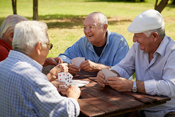Group of senior men, smiling and playing cards at the park Active retirement, old people and seniors free time, group of four elderly men having fun and playing cards game at park. Waist up retirement community stock pictures, royalty-free photos & images
