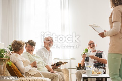 istock Group of senior nursing home pensioners sitting together at common living room listening to young nurse 1149259674