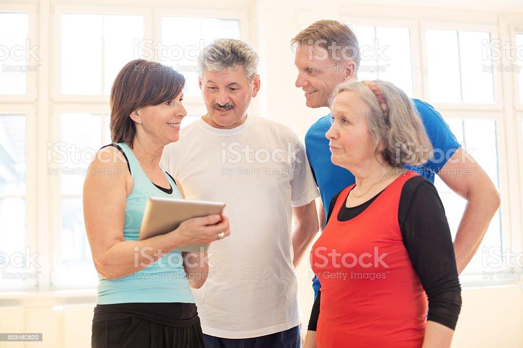 Group of senior people checking fitness progress on digital tablet stock photo