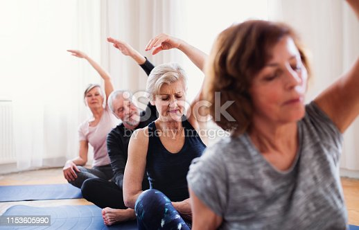 istock Group of senior people doing yoga exercise in community center club. 1153605990