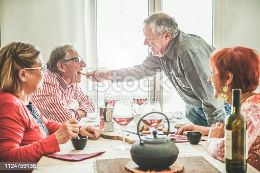 Group of senior people drinking italian style moka coffee and tea after lunch - Mature happy friends eating biscuits and laughing together - Focus on right man face - Joyful elderly lifestyle concept