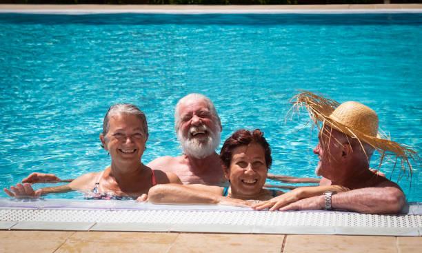 gruppe von senioren freunde lachen genießen das schwimmbad zusammen. helles sonnenlicht und transparentes wasser. großes lächeln und glück - senior bilder wasser stock-fotos und bilder