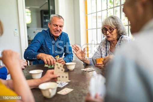 1196170672istockphoto Group of senior people playing cards during tea time 1207050203