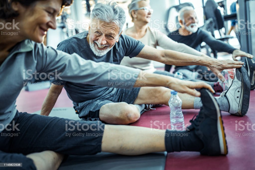 Group Of Senior People Stretching Their Legs In A Gym Stock Photo