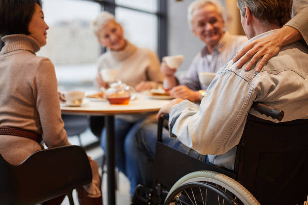 Group of senior people visiting friend in wheelchair: they drinking tea and chatting at home stock photo