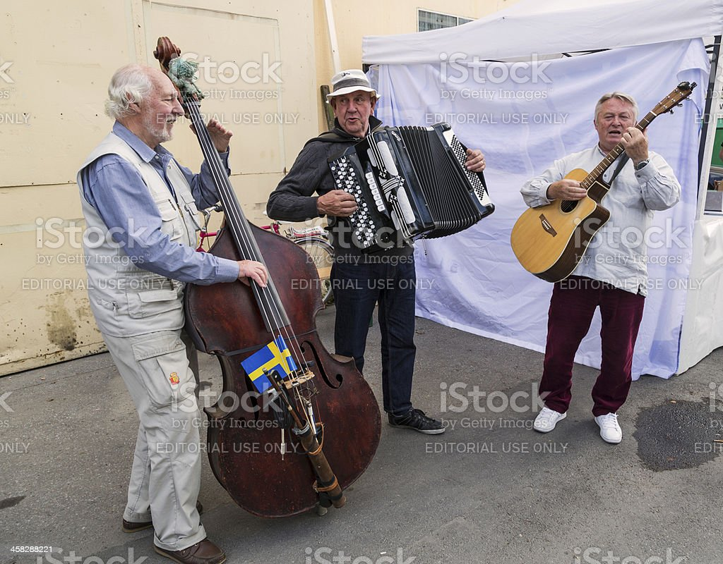 Group of senior playing accordion double bass and guitar outdoors