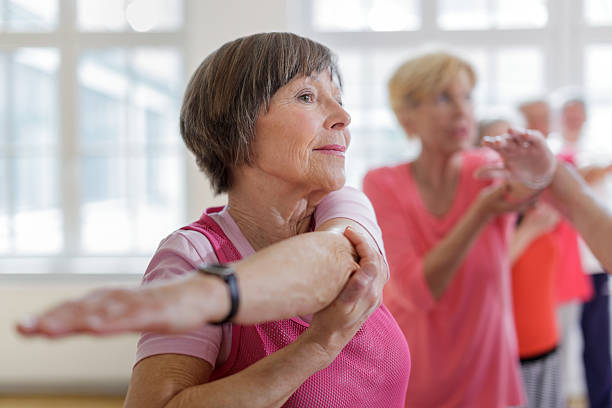 Group of seniors adults with Yoga Instructor Group of seniors adults with Yoga Instructor. Instructor is helping senior woman with a yoga pose. Horizontal shot. 65 69 years stock pictures, royalty-free photos & images