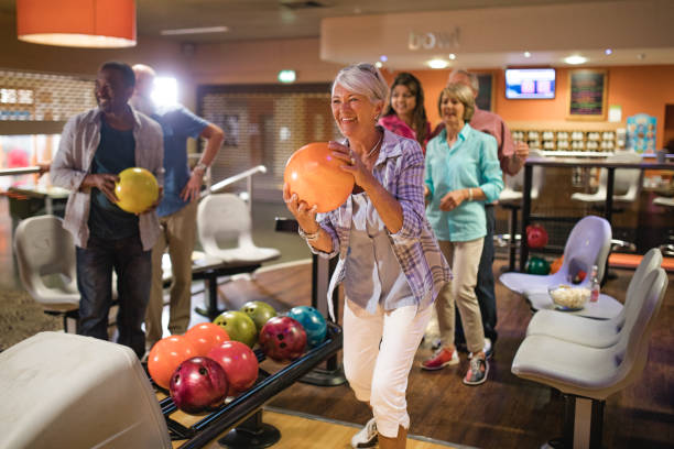 Group of Seniors Bowling Group of seniors at a bowling alley, five senior friends can be seen in the background whilst a woman takes her turn. 65 69 years stock pictures, royalty-free photos & images