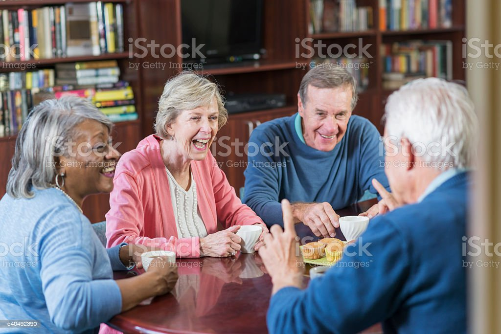 Group of seniors conversing, laughing over coffee stock photo