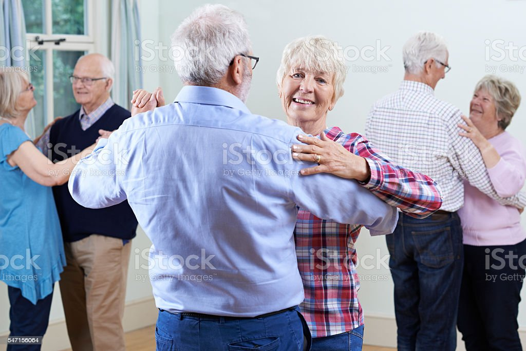 Group Of Seniors Enjoying Dancing Club Together stock photo