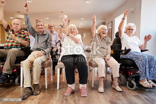 istock Group Of Seniors Enjoying Fitness Class In Retirement Home 1047537236