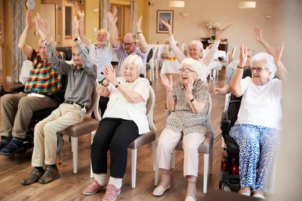 grupa seniorów korzystających fitness klasy w domu emerytalnym - dojrzały zdjęcia i obrazy z banku zdjęć