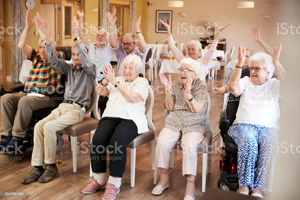 Group Of Seniors Enjoying Fitness Class In Retirement Home стоковое фото