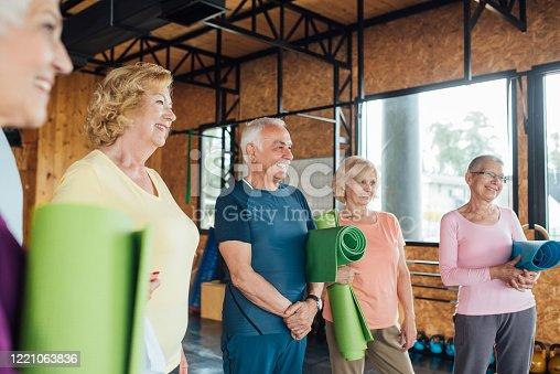 1047537292 istock photo Group of seniors enjoying  friendship before their yoga class 1221063836