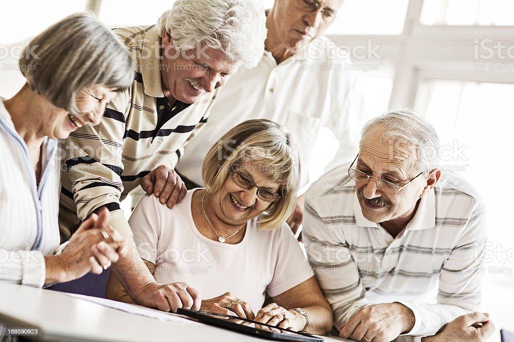 Group of Seniors Examine Digital Tablet royalty-free stock photo