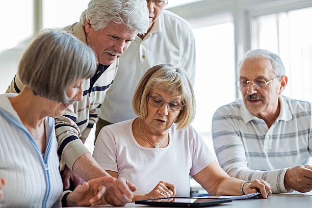 Group of seniors examine digital tablet Group of seniors looking at digital tablet in the classroom. community center stock pictures, royalty-free photos & images