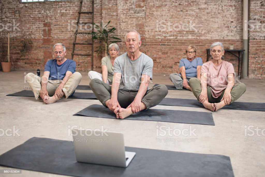 Group of Seniors Exercising Yoga with laptop stock photo