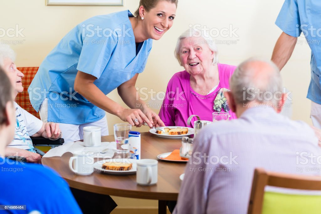 Group of seniors having food in nursing home stock photo