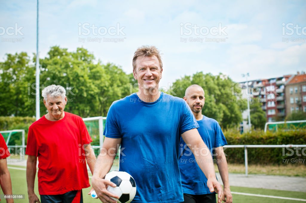Group of seniors in football jersey on the soccer field stock photo